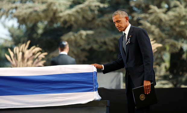 U.S. President Barack Obama touches the casket of former Israeli President Shimon Peres after speaking at his funeral at the Mount Herzl cemetery in Jerusalem